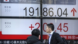 A man and a woman walk past an electronic stock board showing Japan's Nikkei 225 index at a securities firm in Tokyo, Tuesday, March 28, 2017. (AP / Eugene Hoshiko)
