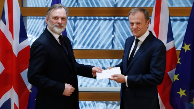 Britain's permanent representative to the European Union Tim Barrow, left, hand delivers PM Theresa May's Brexit letter to EU Council President Donald Tusk, in Brussels, Belgium, on March 29, 2017. (Yves Herman/Pool Photo via AP)