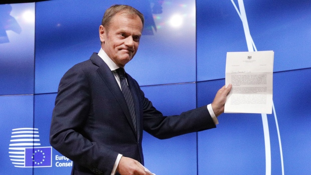 EU Council President Donald Tusk grimaces at a press conference in Brussels, Belgium, Wednesday, March 29, 2017 showing the letter he received signed by Britain's Prime Minister Theresa May formally triggered the beginning of Britain's exit from the European Union. ((AP Photo/Olivier Matthys)
