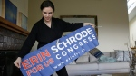 Erin Schrode unfurls a campaign banner at her home in Mill Valley, Calif., on Feb. 21, 2017. (Eric Risberg / AP)