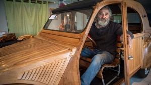 Michel Robillard poses in his handbuilt wooden 2CV Citroen car, on March 20, 2017. (Guillame Souvant / AFP)