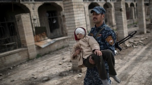 A federal police officer carries an injured boy through a destroyed train station during fighting between Iraqi security forces and Islamic State militants, on the western side of Mosul, Iraq, Sunday, March 19, 2017. (AP Photo/Felipe Dana)