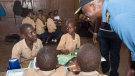 Lt.-Cmdr. Paul Smith, Commanding Officer of HMCS Summerside, talks to students at St. Edwards Primary School in Freetown, Sierra Leone, on March 21, 2017 (THE CANADIAN PRESS/HO-DND-Master Cpl. Pat Blanchard)