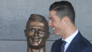 Cristiano Ronaldo with a bust in his likeness at the Madeira international airport outside Funchal on March 29, 2017. (Armando Franca / AP)