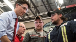 Prime Minister Justin Trudeau speaks with Saskatchewan Polytechnic students Dillon Frater, right, and Garrett Anderson in the Agricultural Equipment Shop of Sask Polytech in Saskatoon, Wednesday, March 29, 2017. THE CANADIAN PRESS/Liam Richards