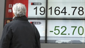 A man looks at an electronic stock board showing Japan's Nikkei 225 index at a securities firm in Tokyo, Thursday, March 30, 2017. (AP / Eugene Hoshiko)