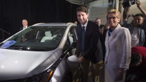 Justin Trudeau's post-budget tour continues today through Ontario's industrial heartland, where the prime minister will spell out what his federal Liberal government is doing to help foster innovation in Canada's auto sector. Prime Minister Justin Trudeau, left, and Ontario Premier Kathleen Wynne pose as they plug in an electric vehicle at the General Motors plant in Oshawa, Ont., in a June 10, 2016, file photo. (Chris Young/THE CANADIAN PRESS)