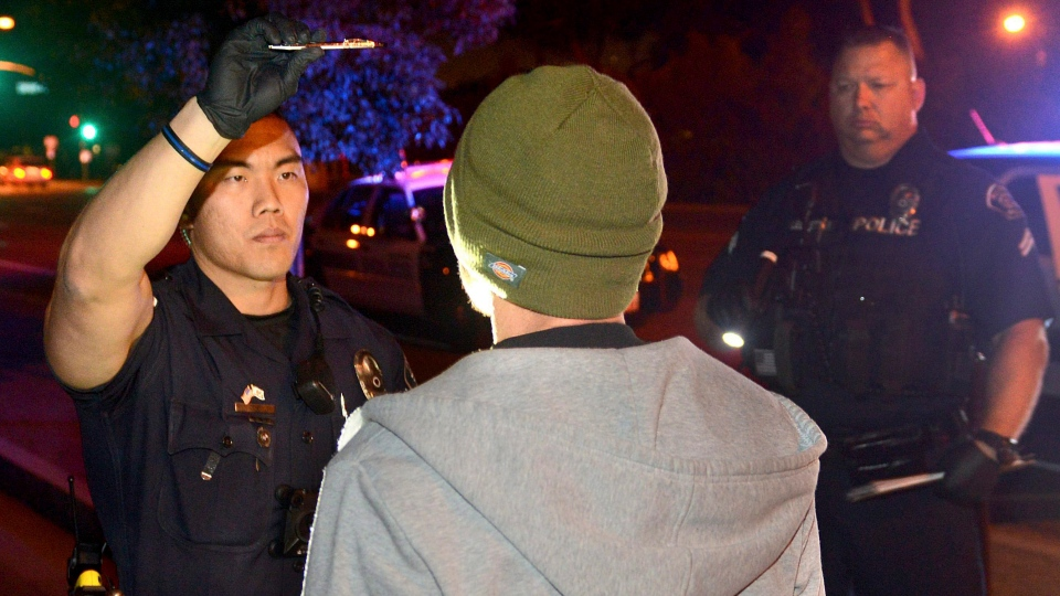 FILE -- In this Saturday, Nov. 19, 2016 photo, Fullerton police officer Jae Song, left, conducts a field sobriety test on driver suspected of driving while impaired by marijuana in Fullerton, Calif. (Bill Alkofer/The Orange County Register/SCNG via AP)