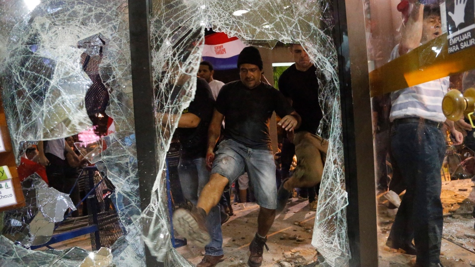 A man breaks a window of the Congress building during a protest against presidential re-elections, in Asuncion, Paraguay, Friday, March 31, 2017. (AP Photo/Jorge Saenz)