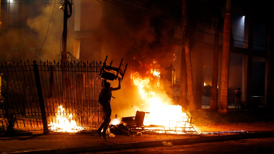 A protester carries a chair to a fire outside the congress building during clashes between police and protesters in Asuncion, Paraguay, Friday, March 31, 2017. (AP Photo/Jorge Saenz)