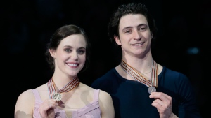 Tessa Virtue and Scott Moir, of Canada, show off their gold medals during victory ceremony at the World figure skating championships in Helsinki, Finland, on Saturday, April 1, 2017. (AP Photo/Ivan Sekretarev)