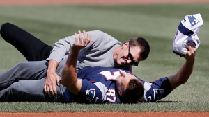 New England Patriots quarterback Tom Brady, top, tackles teammate Rob Gronkowski after he ran with Brady's recovered Super Bowl jersey as they joke around during Boston Red Sox Home Opening Day ceremonies at Fenway Park, Monday, April 3, 2017, in Boston. (Elise Amendola / AP)