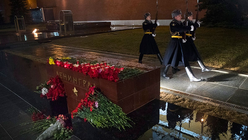 The Kremlin guards in Moscow change next to candles and flowers placed in memory of victims killed by a bomb blast in a subway train in St. Petersburg at the memorial stone with the word Leningrad (St. Petersburg) at the Tomb of Unknown Soldier in front of the Kremlin wall Monday, April 3, 2017. (AP Photo/Pavel Golovkin)