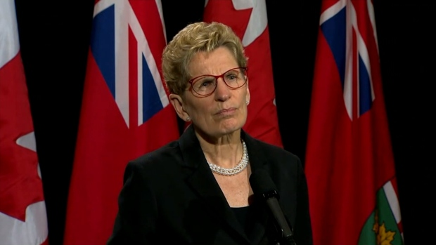 Premier Kathleen Wynne speaks with reporters at Queen's Park on Tuesday.