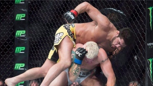Patrick (The Predator) Cote (top) lands a blow to the head of Joe Riggs, from the United States, during their UFC 186 welterweight fight in Montreal, Saturday, April 25, 2015. (Graham Hughes/The Canadian Press)