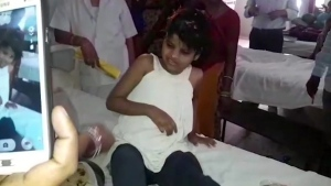 A young Indian girl sits on a bed in a hospital in this image taken from video in Bahraich northern India, on April 6, 2017. (KK Productions, via AP)