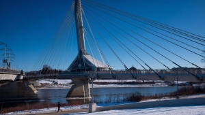 FILE -- A woman runs on a path while the Provencher pedestrian bridge towers above her, in Winnipeg, Man., on Monday, Nov. 30, 2015. (THE CANADIAN PRESS/Darryl Dyck)