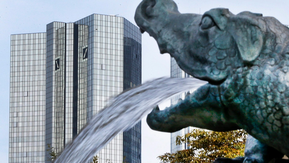 In this Oct. 11, 2016 file photo, water spills out of a small dragon sculpture on a fountain with the headquarters of the Deutsche Bank in background in Frankfurt, Germany, (AP / Michael Probst)