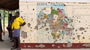In this Tuesday, Nov. 15, 2016 file photo, students line up outside a classroom with a map of Africa on its wall, in Yei, in southern South Sudan. (AP Photo/Justin Lynch, File)