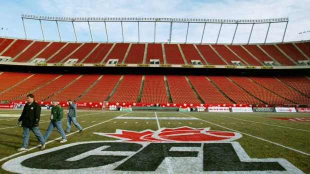 In this file photo, workers walk across the field next to the new CFL logo at centerfield at Commonwealth Stadium in Edmonton Thursday, November 21, 2002. (CP PHOTO/Kevin Frayer)