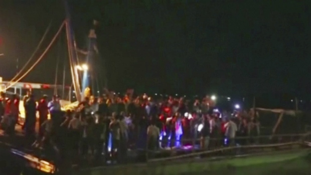 In this Friday, April 7, 2017 image made from a video provided by DVB, people gather following news of a ferry sinking, in Pathein, Myanmar. (DVB via AP)