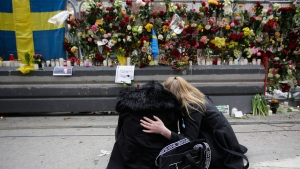 Women sit in front of a fence covered with flowers near the department store Ahlens following a suspected terror attack in central Stockholm, Sweden on Saturday, April 8, 2017. (AP / Markus Schreiber)