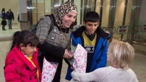 Fatmeh Ayash, daughter Sedra, left, and son Mohammad, from Syria, are greeted with flowers as they arrive at the airport in Halifax on Monday, February 29, 2016. (THE CANADIAN PRESS/Andrew Vaughan)