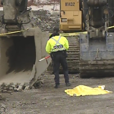 The body of a 19-year-old worker is covered by a yellow tarp after a workplace accident at a Kanata job site, Wednesady, March 18, 2009.