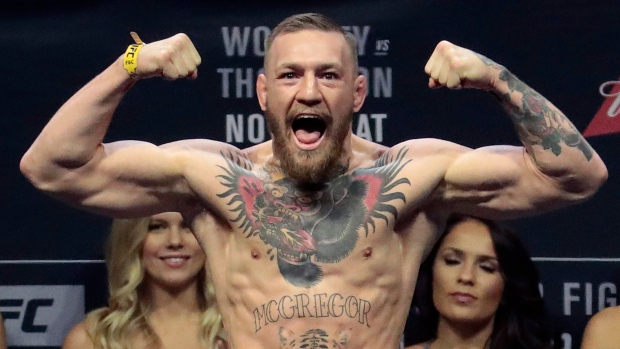 In this Nov. 11, 2016, file photo, Conor McGregor stands on a scale during the weigh-in event  in New York. (AP Photo/Julio Cortez, File)