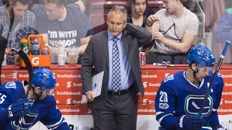 Vancouver Canucks head coach Willie Desjardins, centre, stands on the bench behind Michael Chaput, left, and Brandon Sutter during third period NHL hockey action against the Edmonton Oilers, in Vancouver, B.C., on Saturday, April 8, 2017. THE CANADIAN PRESS/Darryl Dyck