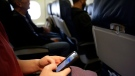 A passenger check her cell phone before a flight, in Boston, on Thursday, Oct. 31, 2013. (AP Photo/Matt Slocum)