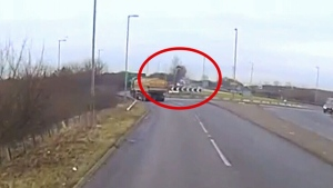 The video shows the car colliding mid-air with a tree planted in the centre of the roundabout before crashing to the ground on the other side.