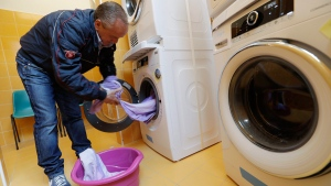 Ciro Guardaccione using a washing machine in a laundry opened in a catholic community in Rome, on April 11, 2017. (Alessandra Tarantino / AP)