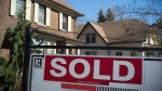 A sold sign is shown in front of west-end Toronto homes Sunday, April 9, 2017. (Graeme Roy/The Canadian Press)