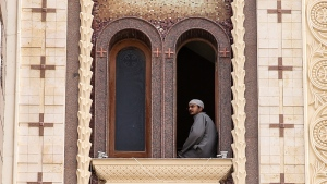 A man looks out of a church window during the funeral for those killed in a Palm Sunday church attack in Alexandria, Egypt, at the Mar Amina church, Monday, April 10, 2017. (AP / Samer Abdallah)