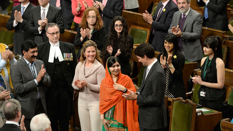 Prime Minister Justin Trudeau, right, and his wife Sophie Gregoire Trudeau, centre left, clap as Pakistani activist and Nobel Peace Prize winner Malala Yousafzai, centre, is paid tribute in the House of Commons on Parliament Hill in Ottawa on Wednesday, April 12, 2017. (Adrian Wyld / THE CANADIAN PRESS)