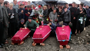 Ossetians weep over the coffins of hostages killed in the school siege during a funeral in Beslan, Northern Ossetia, Russia, Monday Sept. 6, 2004. (AP / Ivan Sekretarev)