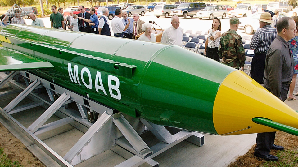 A group gathers around a GBU-43B, or massive ordnance air blast (MOAB) weapon, on display at the Air Force Armament Museum on Eglin Air Force Base near Valparaiso, Fla. on May 2004. (Mark Kulaw / Northwest Florida Daily News)