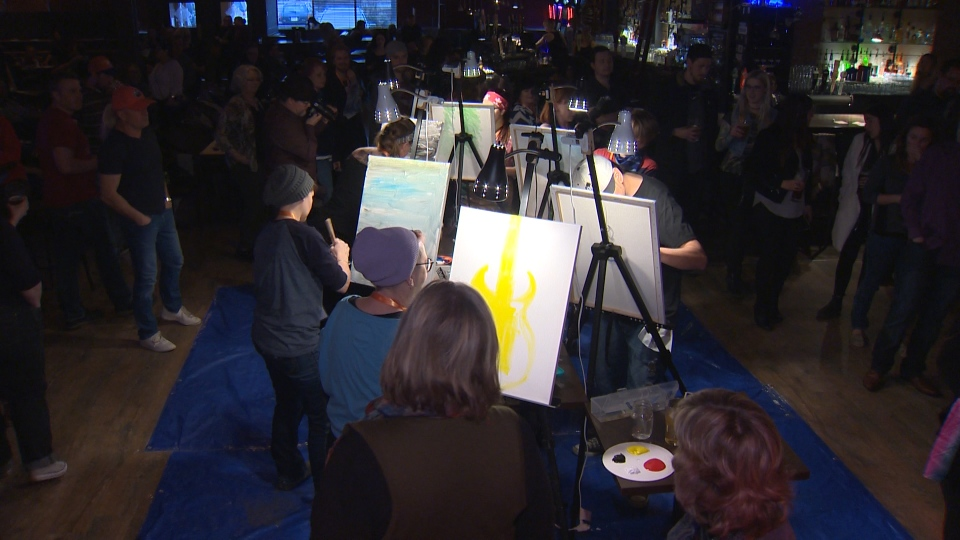 Painters competing in Red Deer's 20-minute Art Battle.