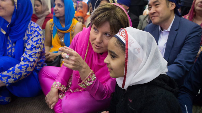 Liberal leader Christy Clark, centre left, speaks with Avneet Gill, 11, during a Vaisakhi event at the Khalsa Diwan Society Sikh Temple in Vancouver, B.C., on Saturday, April 15, 2017. (THE CANADIAN PRESS/Darryl Dyck)