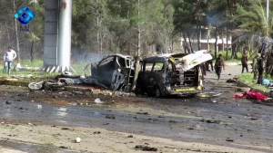 This frame grab from video provided by the Thiqa News Agency, shows rebel gunmen at the site of a blast that damaged several buses and vans at the Rashideen area, a rebel-controlled district outside Aleppo city, Syria, Saturday, April. 15, 2017. A human rights group says 126 people were killed Saturday in an explosion that hit near buses carrying evacuees from two towns besieged by rebels nearby. (Thiqa News via AP)