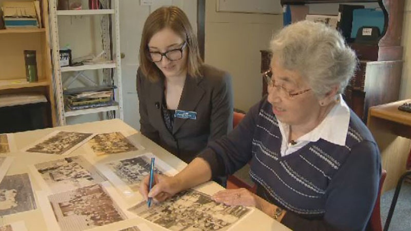 Museum curator Lyne Allain and Mahone Bay resident Beverly Eisnor sort through photos at the Mahone Bay Museum.