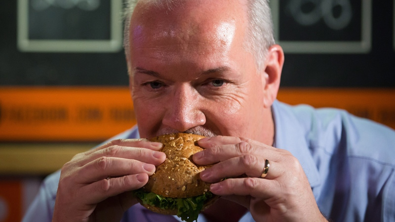 NDP Leader John Horgan takes a bite of the burger bearing his name during a campaign stop at Burger Heaven in New Westminster, B.C., on Monday April 17, 2017. THE CANADIAN PRESS/Darryl Dyck