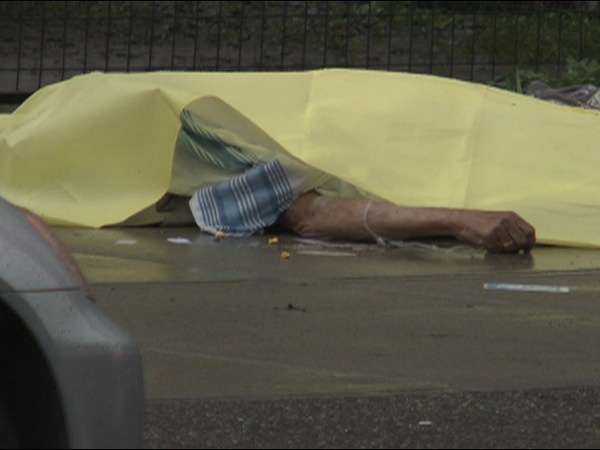 A tarp lies over an unidentified man after he was shot and killed by Vancouver Police on March 20, 2009.