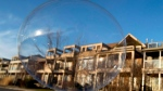 A Toronto neighbourhood is seen through a soap bubble on Sunday April 9, 2017. There is growing concern that the Toronto real estate market is in a bubble condition. (THE CANADIAN PRESS/Frank Gunn)