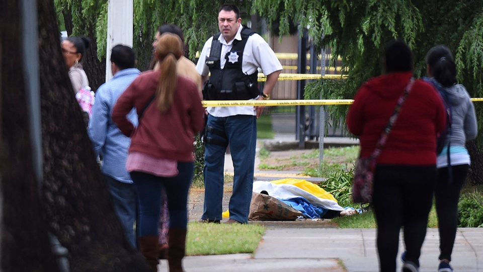 A Fresno police detective stands over the body of one of the three shooting victims in Fresno, Calif., on Tuesday, April 18, 2017. (John Walker/Fresno Bee via AP)