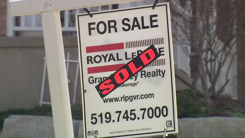 A 'sold' sticker covers a 'for sale' sign outside a home in Waterloo.