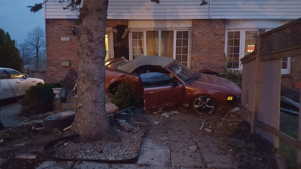 A Ford Mustang struck two townhouses in east London on Wednesday, April 19, 2017. (Justin Zadorsky / CTV London)