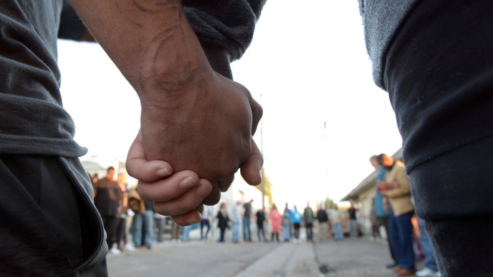 Community members and faith leaders from On Ramps Covenant Church hold hands during a prayer and vigil in the alley behind the Catholic Charities' Fresno Family Resource Center on April 18, 2017. (Silvia Flores/The Fresno Bee via AP)