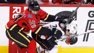 Anaheim Ducks' Andrew Cogliano, right, is hit by Calgary Flames' Matt Bartkowski during second period NHL playoff action in Calgary, Alta., April 17, 2017. (Larry MacDougal/The Canadian Press)